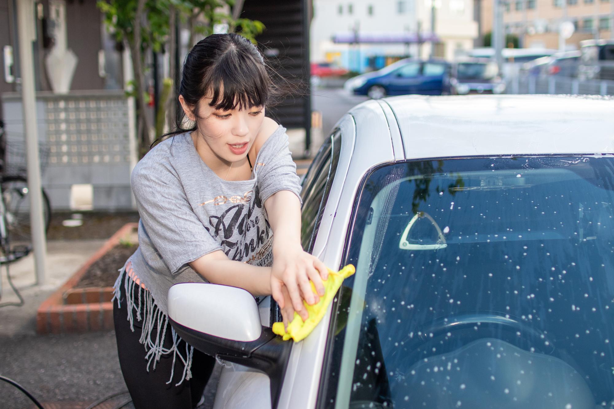 女性が洗車している画像